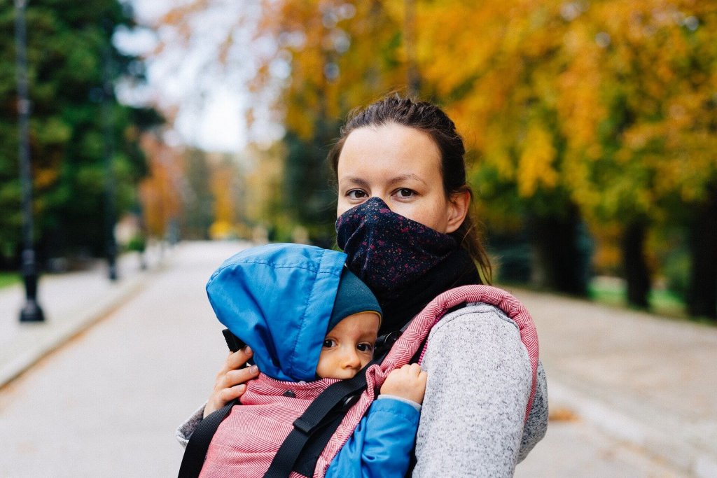 Frau mit Gesichtmaske und Baby in der Tragetasche.