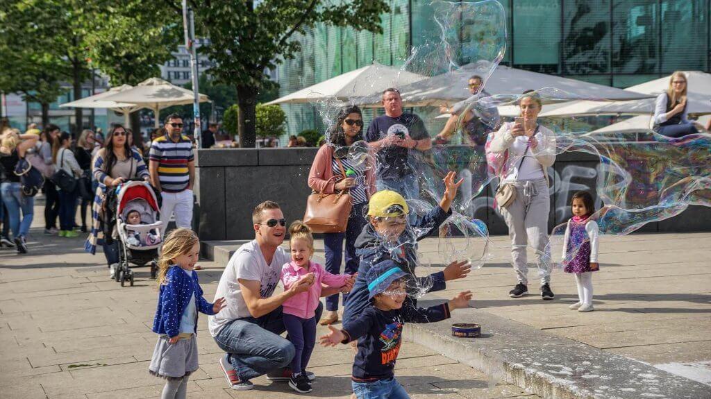 Kinder auf einem Platz mit Seifenblasen.