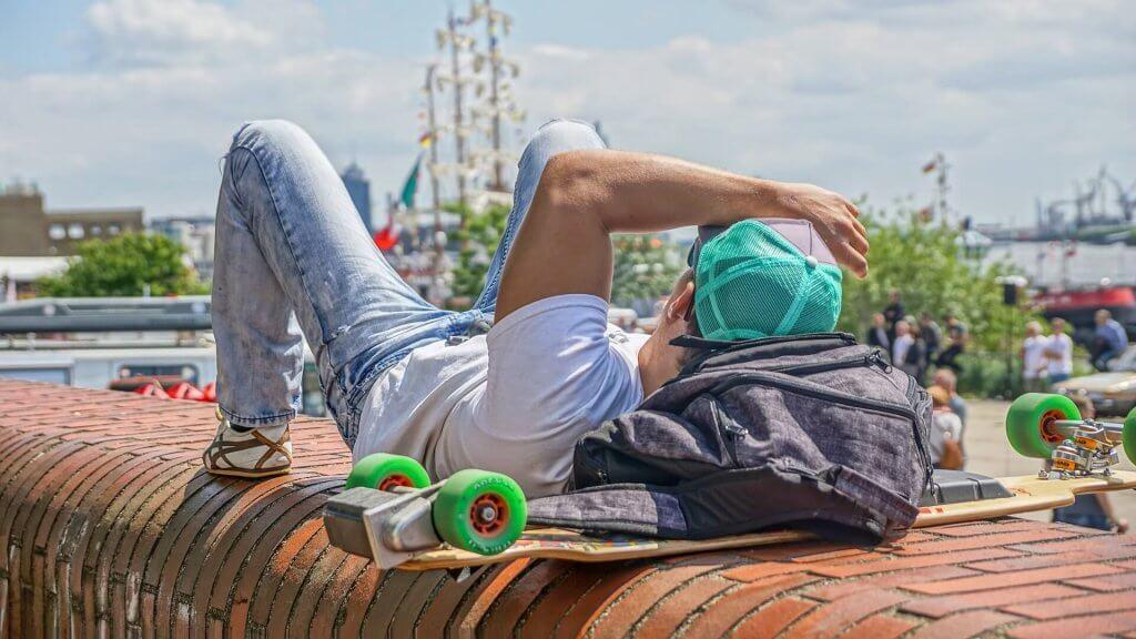 Ein junger Mann und ein Skateboard auf einer Mauer.