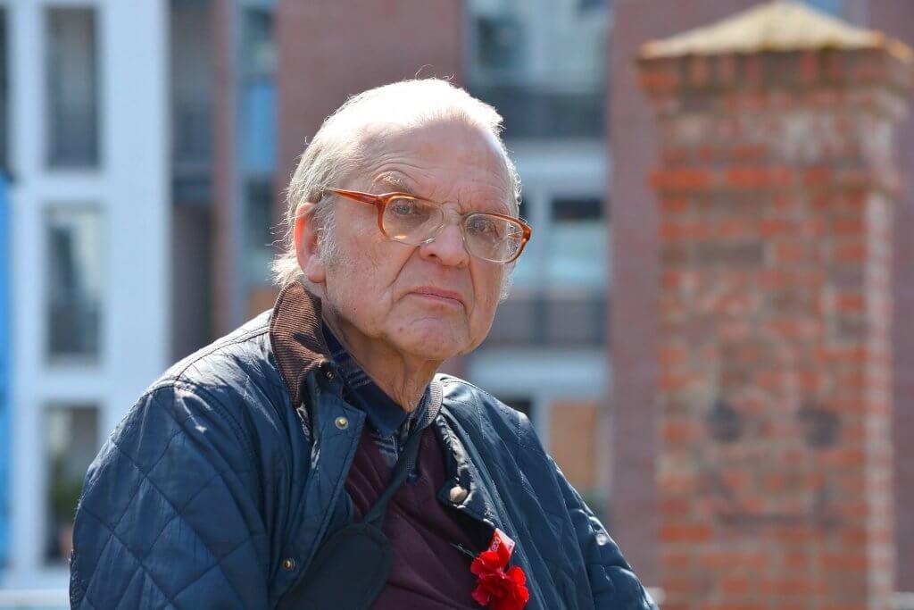Ein älterer Herr mit grauen Haaren, Brille und Steppjacke.
